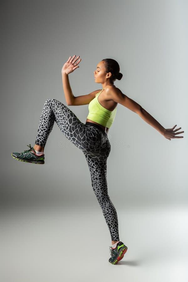 Sportive compétente faisant seuls des exercices de matin dans le studio images libres de droits