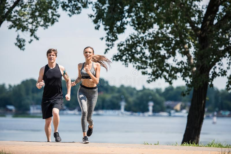 Sportive couple jogging in park royalty free stock images