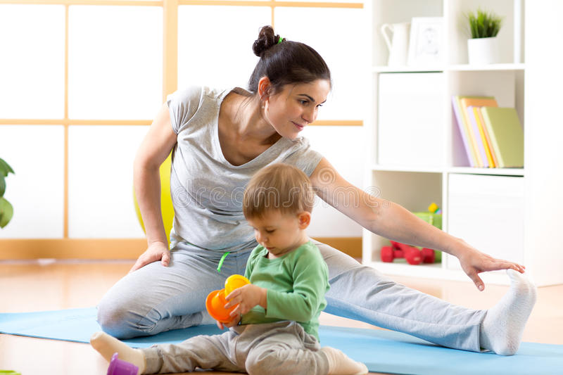 Sportive cute woman is engaged in fitness and yoga at home. Her son kid by near sitting and playing. Sportive women is engaged in fitness and yoga at home. Her stock image