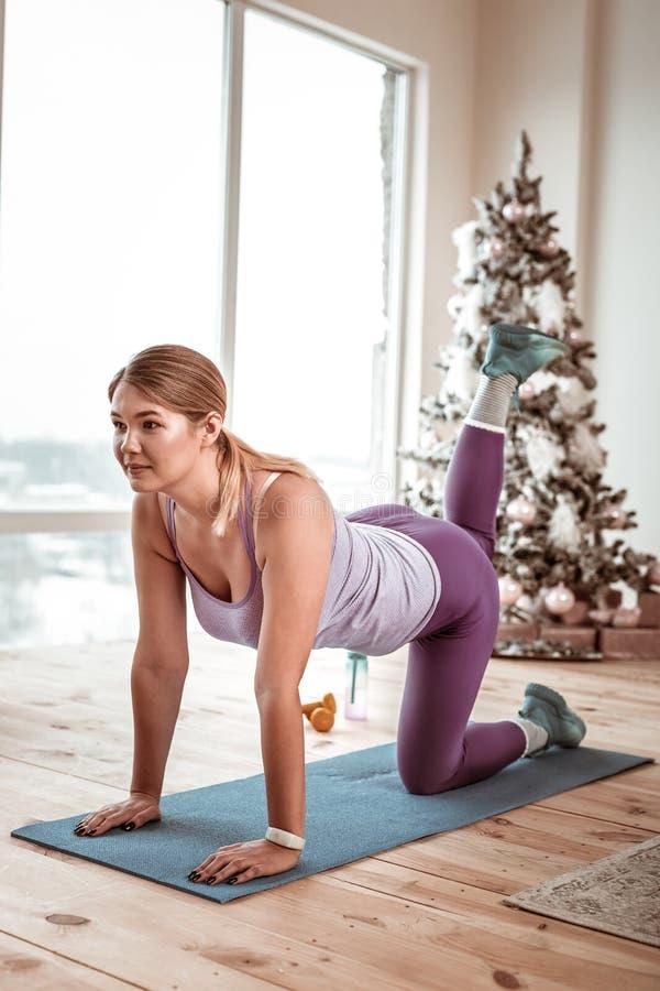Sportive dam i violett skinande damasker som gör plankan på mattt gummi royaltyfri foto