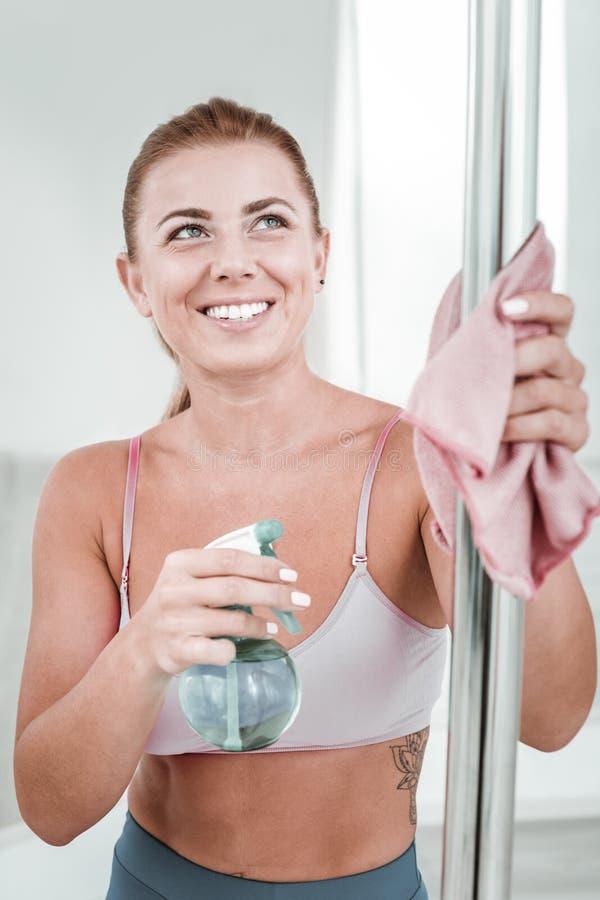 Sportive de sourire nettoyant son poteau avant l'exercice image stock