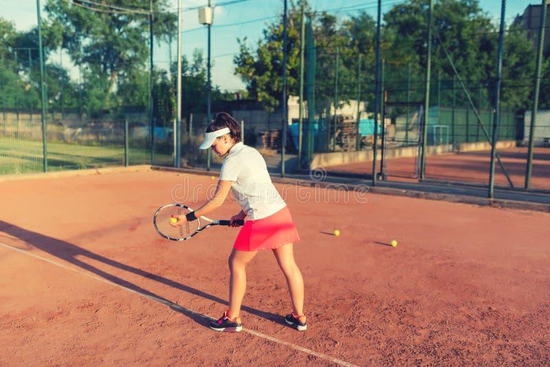 Sportive de tennis jouant sur la cour d'argile Forme physique saine, fille atractive jouant le tennis photo libre de droits