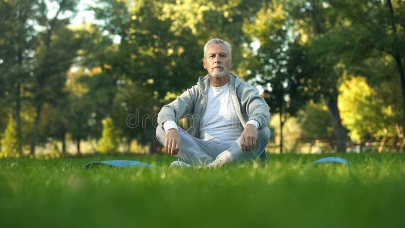 Sportive dorośleć mężczyzny relaksującego i odpoczywa w parku, siedząca lotosowa poza na joga macie zdjęcie royalty free