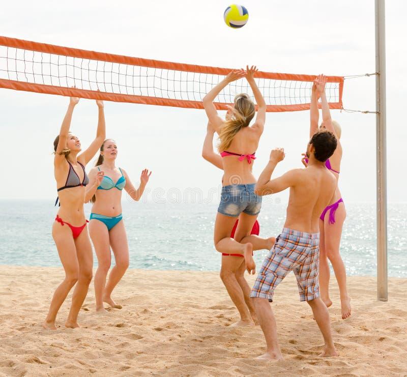 Sportive folk som spelar salva på stranden royaltyfri bild
