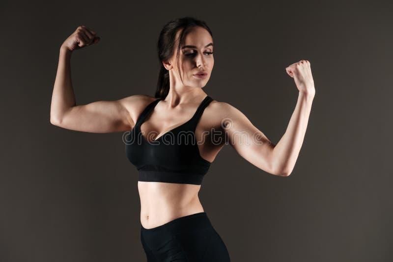 Sportive forte sérieuse montrant le biceps photographie stock