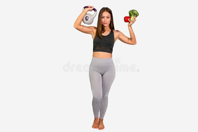 Sportive Frau in den Leggins, die Früchte und VE halten Weibliches Modell FFitness mit Kesselglocke stockfotografie