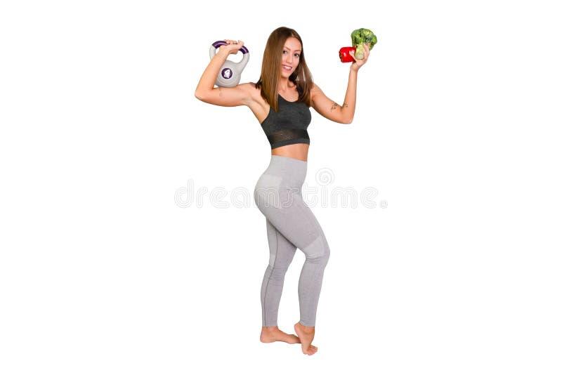 Sportive Frau in den Leggins, die Früchte und VE halten Weibliches Modell FFitness mit Kesselglocke stockbilder
