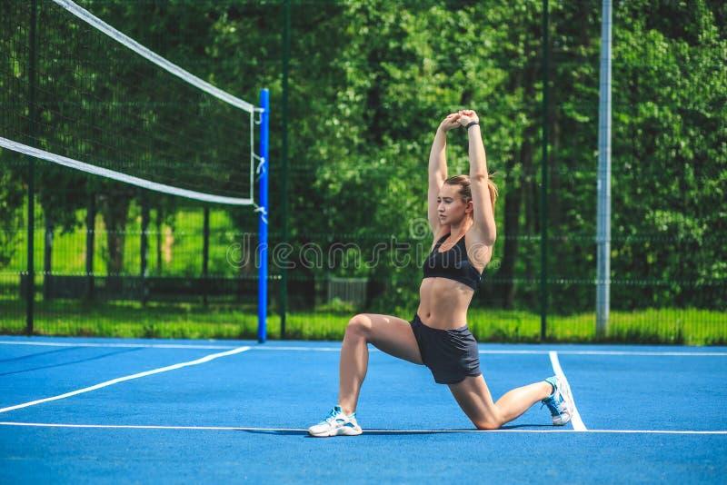 Sportive Frau, die auf dem blauen Tennisplatz in Park Moskaus Yauza ausdehnt und ausarbeitet lizenzfreie stockfotos