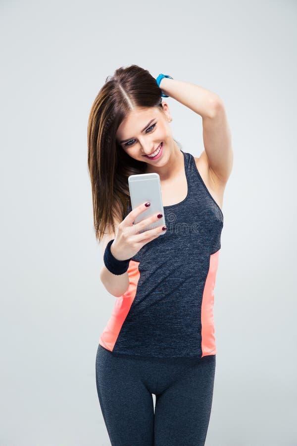 Sportive Frau, die Smartphone verwendet stockfotos