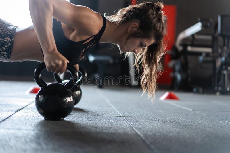 Sportive Frau, die StoßUPS in der Turnhalle unter Verwendung der kettlebells tut lizenzfreies stockbild