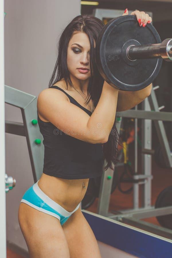 Sportive Frau mit Barbell in der Turnhalle lizenzfreies stockbild
