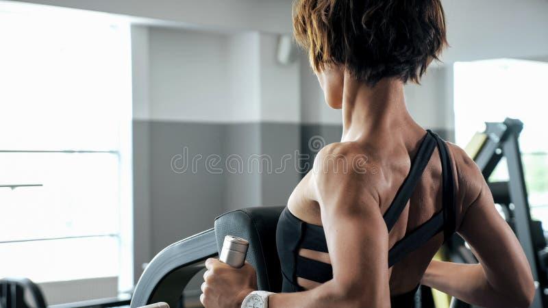 Sportive Frau tut Übungen für Dornmuskeln auf Blocksimulator lizenzfreie stockfotografie