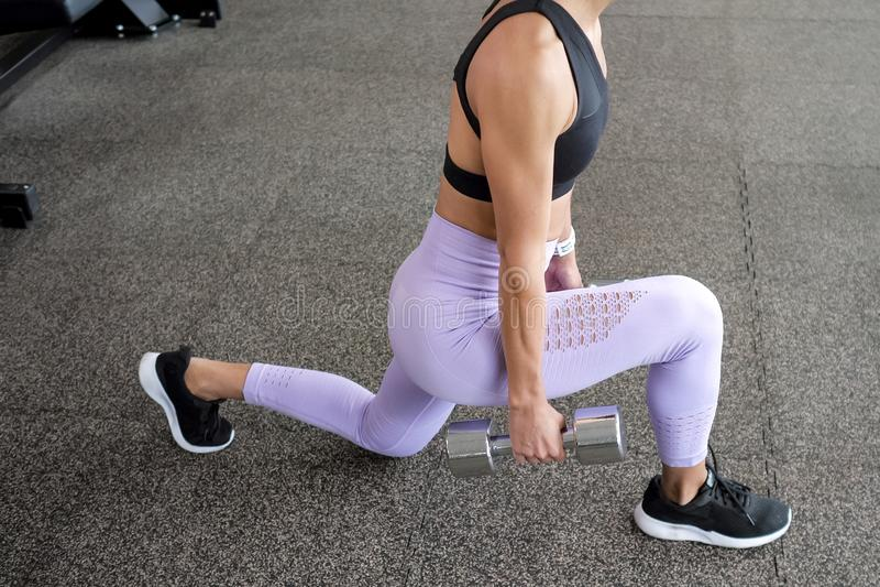 Sportive Frau tut Laufleinen für Beine mit Dummköpfen in ihren Händen in der Turnhalle, Beinnahaufnahme lizenzfreie stockfotografie