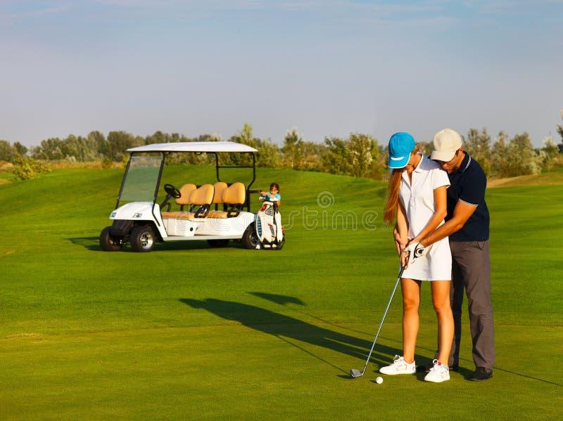 Sportive glückliche Familie, die Golf spielt lizenzfreie stockfotografie