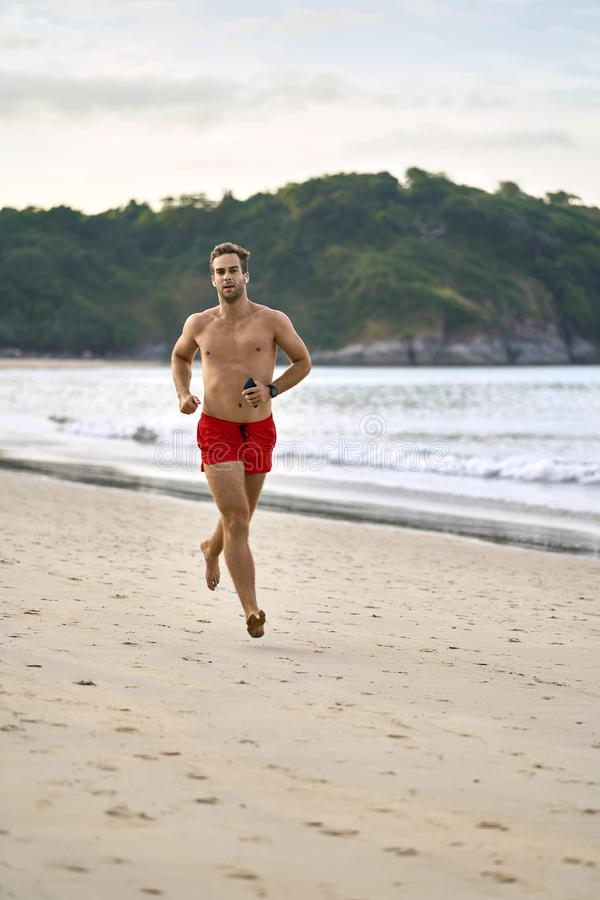 Sportive guy runs on beach. Tanned sportive man is running on the sand beach on the background of the sea and the green hills and the cloudy sky. He wears a red stock photography