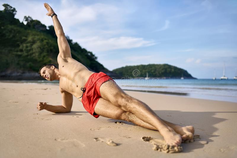 Sportive guy training on beach. Pretty tanned man does a side plank on the sand beach on the sunny background of the sea with white boats and the blue sky. He stock images