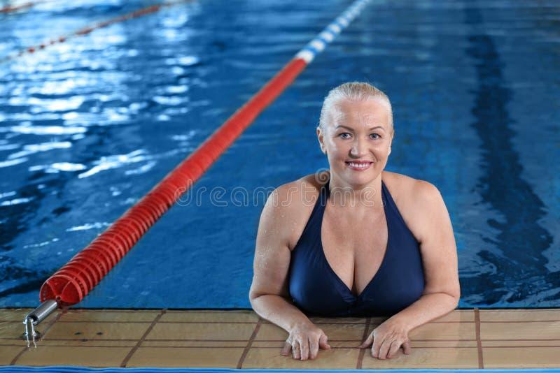 Sportive hög kvinna i inomhus pöl royaltyfri fotografi