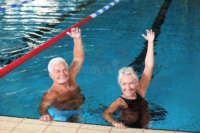 Sportive höga par som gör övningar arkivbild