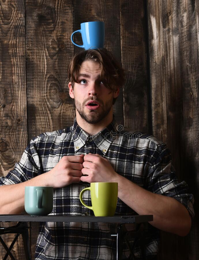 Handsome guy holding cups on wooden background stock photo