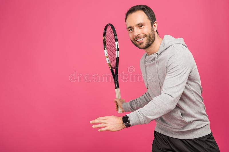 Sportive handsome tennis player with racket, isolated. On pink stock photos