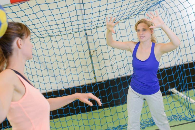 Sportive jugeant la boule contre le champ de handball d'intérieur photos stock