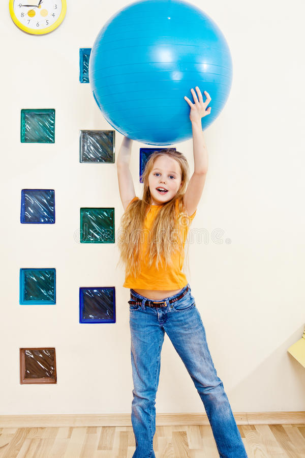 Sportive kid. Holding large gymnastic ball up high royalty free stock photography