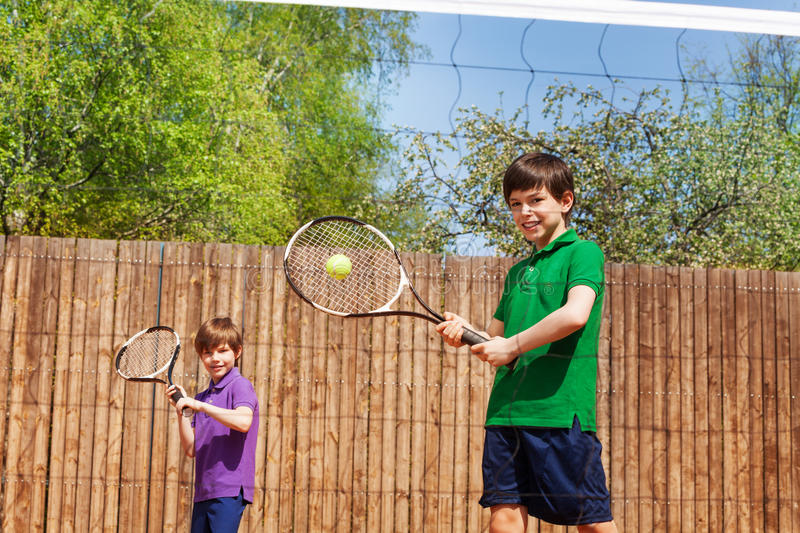 Sportive kid boy hitting forehand in tennis. Double tennis partners, kid boys, playing together outside in summer, view through the tennis net stock photos