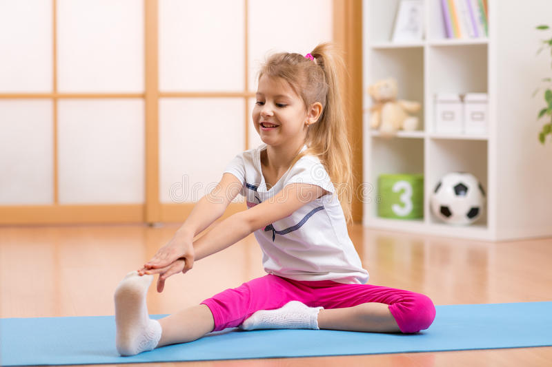 Sportive kid doing gymnastic at home. Sportive kid girl doing gymnastic at home stock images