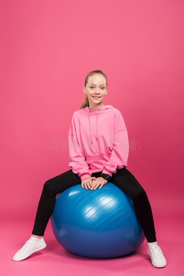 Sportive kid sitting on fitness balls, isolated. On pink royalty free stock images