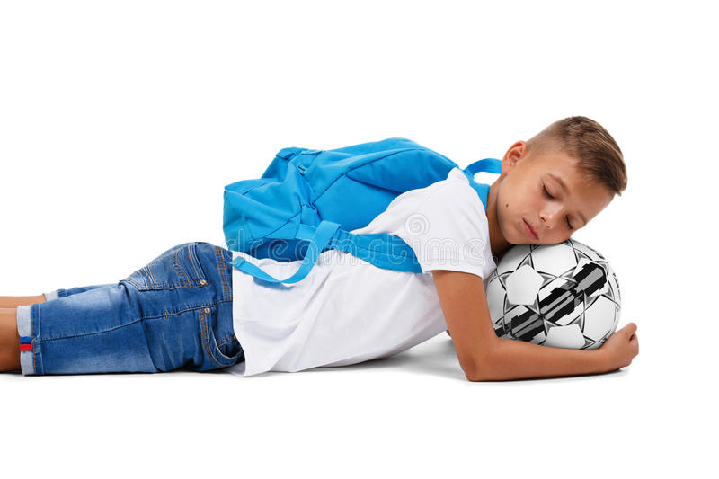 A sportive kid with a soccer ball lying on the ground. A little footballer isolated on a white background. A little boy with a head on a ball. A cute tired royalty free stock images