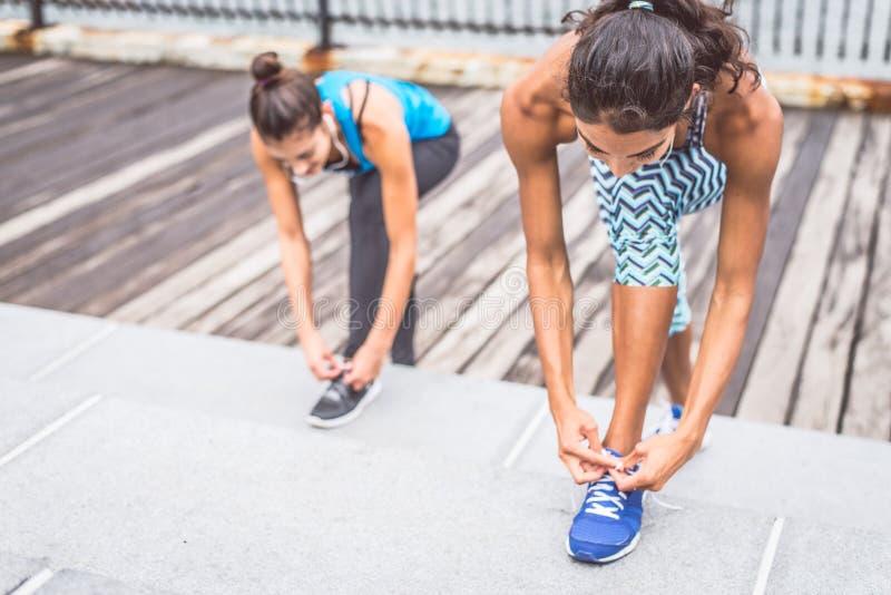 Sportive kvinnor som binder skosnöre arkivfoton