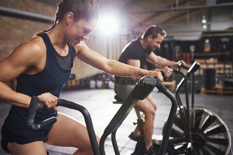 Sportive Leute, die hartes Training auf exercycle tun lizenzfreie stockbilder