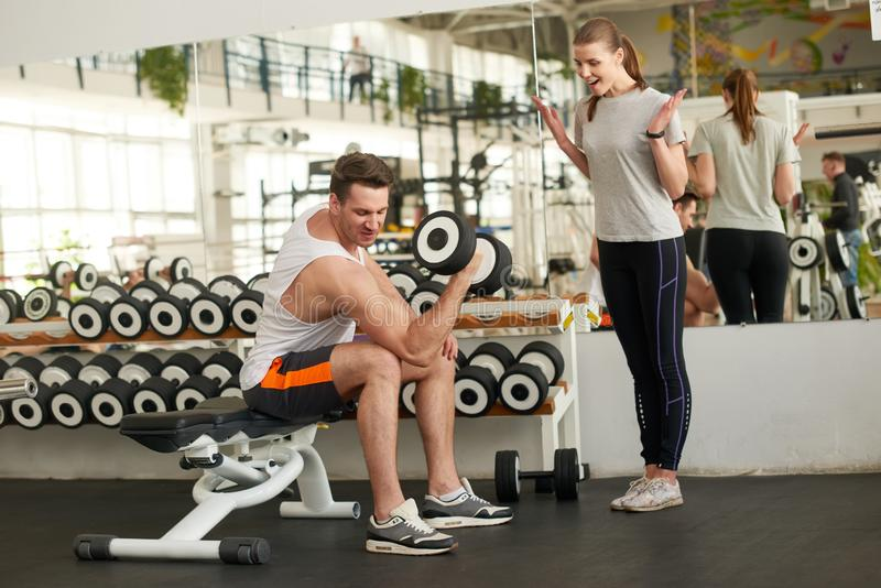 Sportive man flexing muscles with dumbbell. stock image