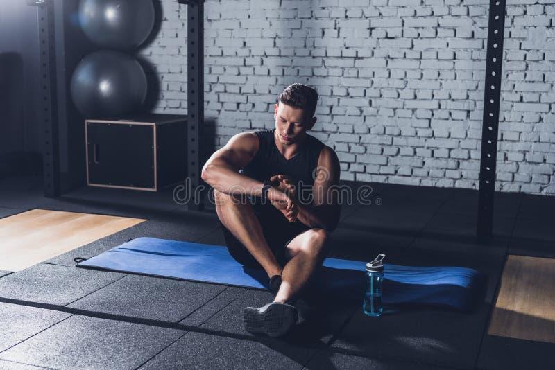 sportive man som ser smartwatch fotografering för bildbyråer