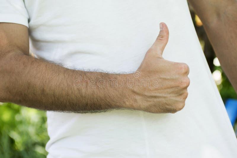 Sportive man som tummar upp i den vita T-tröja royaltyfria bilder