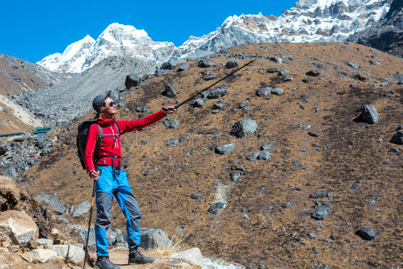 Sportive Man staying on Footpath with walking Sticks and pointing. Sportive Man staying on Footpath with walking Sticks and Backpack pointing toward Mountain royalty free stock photos