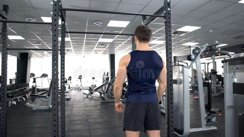 Sportive man warming up before gym workout, fitness lifestyle, bodybuilding stock photo