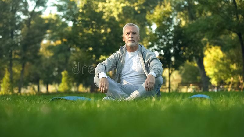 Sportive mature man relaxing and resting in park, sitting lotus pose on yoga mat royalty free stock photo