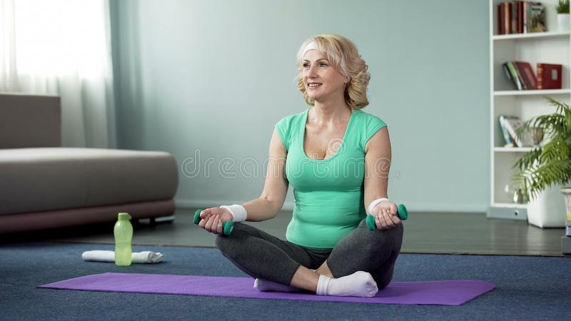 Sportive middle-aged woman holding dumbbells, sitting on mat, home exercises royalty free stock photo