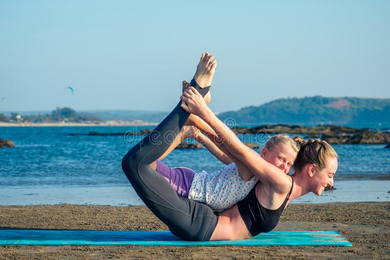 Sportive mother and charming daughter doing stretching exercises on the beach stock images