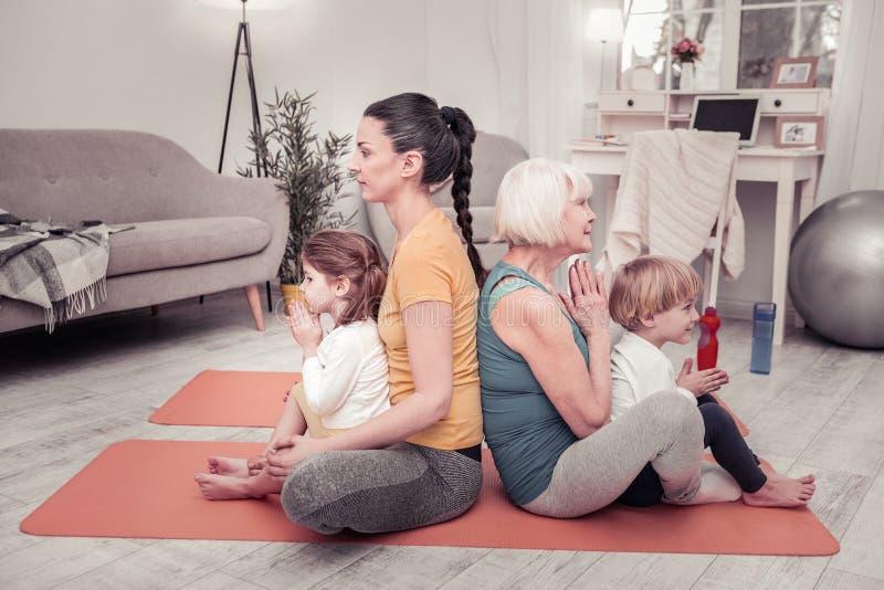 Sportive och aktiv familj som tillsammans gör morgonyoga royaltyfri bild