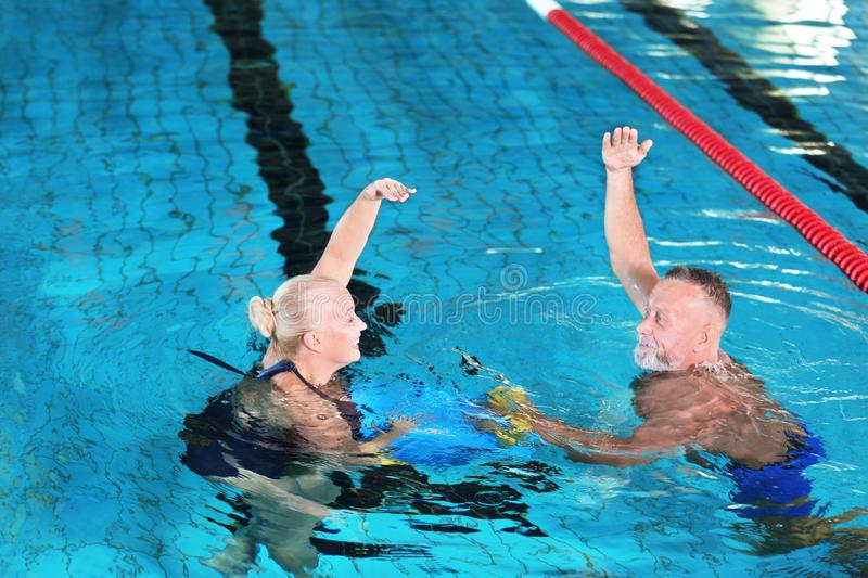 Sportive senior couple doing exercises. In indoor swimming pool stock image