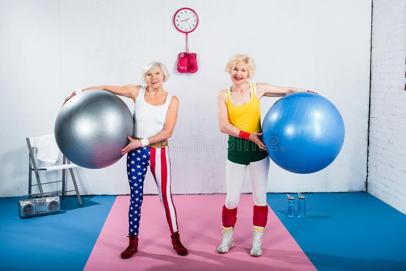 Sportive senior ladies holding fitness balls and smiling at camera. In gym royalty free stock photography