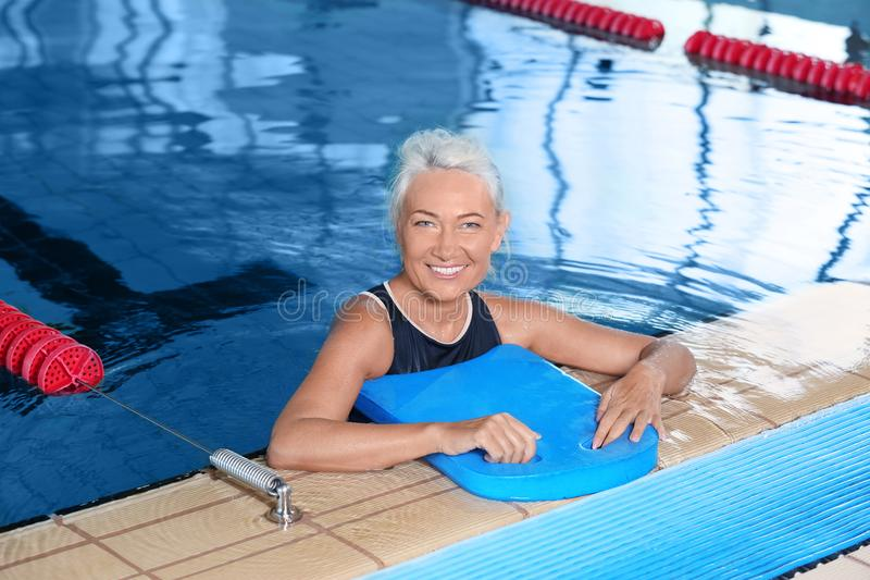 Sportive senior woman in indoor pool royalty free stock photo