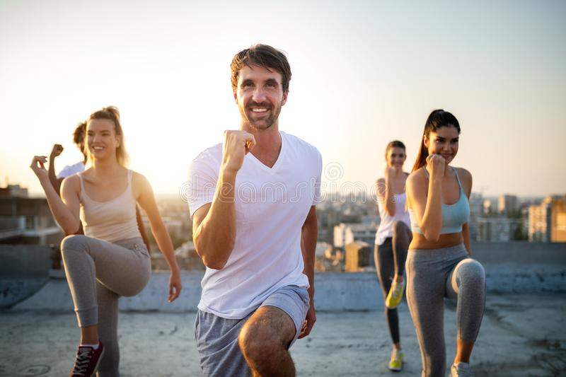 Group of athletic young people, friends in sportswear doing exercises. Sport outdoors royalty free stock photos