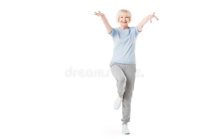 Sportive supérieure se tenant sur une jambe photos libres de droits