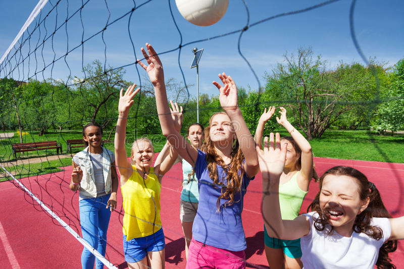 Sportive teenagers are playing volleyball together royalty free stock images