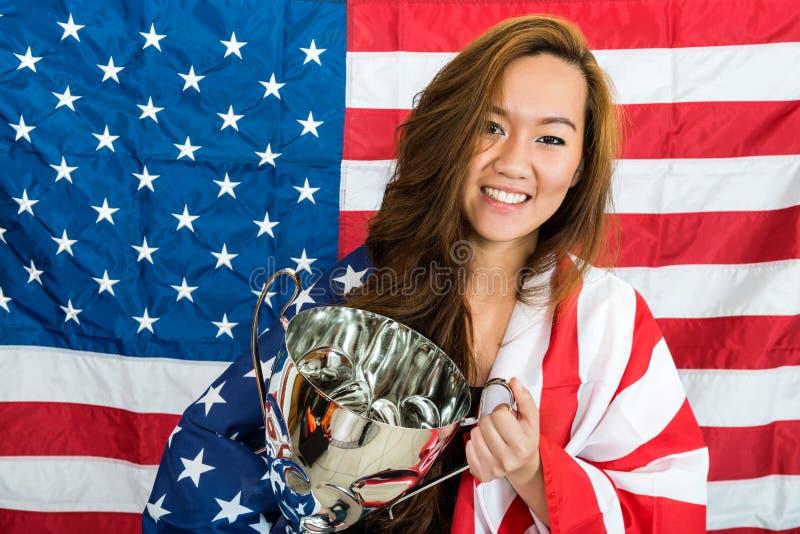 Sportive tenant le trophée contre le drapeau nord-américain images libres de droits