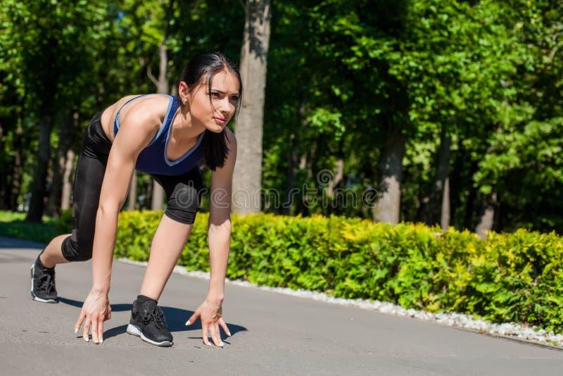 Sportive tonårig startande spring i parkera royaltyfri foto