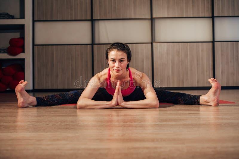 Sportive ung flicka som sträcker ben, yogagrupp kvinnasammanträde tvinnar in royaltyfria foton